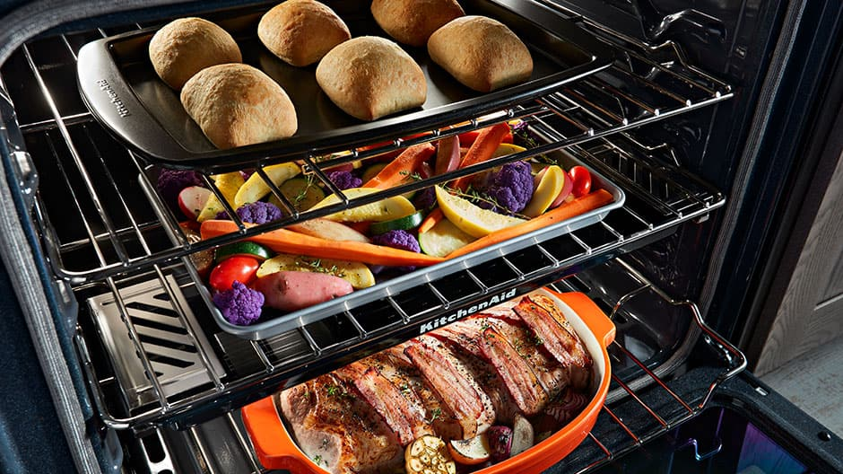 Angled view of open oven showing a bacon-wrapped roast, a tray of roasted vegetables on the steam rack and a tray of rolls on the upper rack.