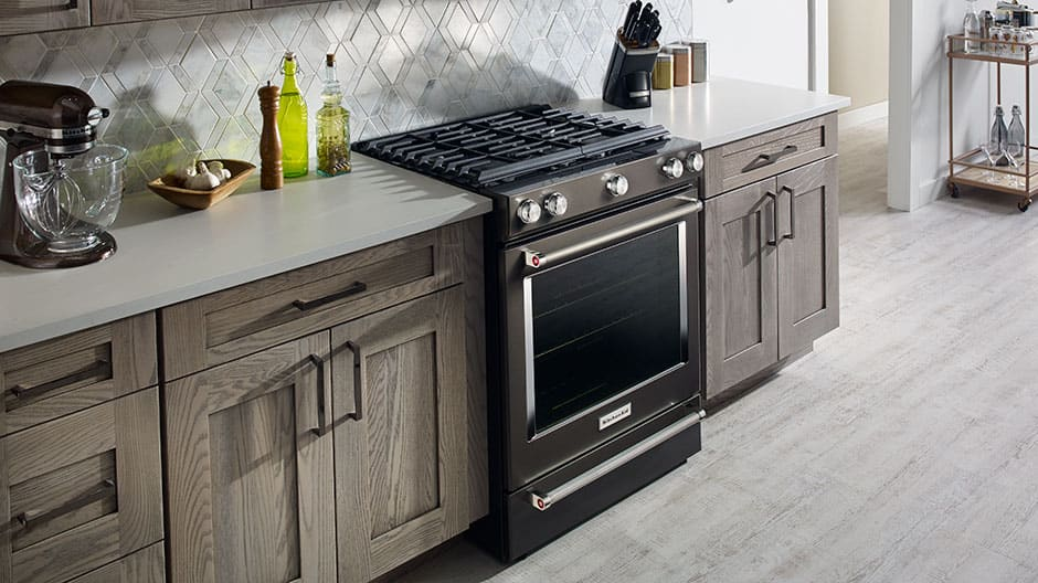 Black stainless steel gas range set in a modern rustic kitchen.