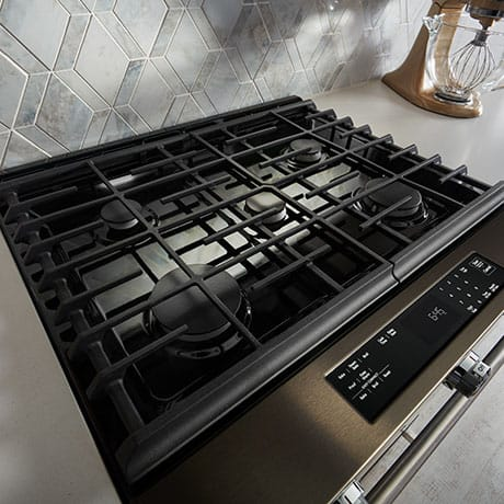 Five burners of various sizes are shown beneath black grates that extend across the black cooktop.