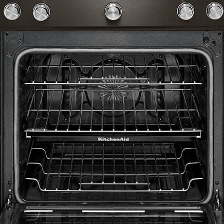 The steam rack is shown in the middle rack position inside the oven. It has a shallow edge to hold water and is inscribed with the KITCHENAID logo.