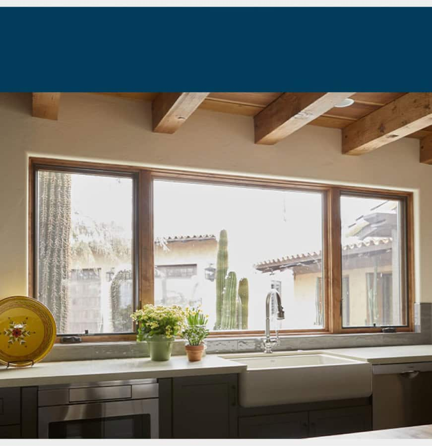 Interior view of warm wood window hue complementing farmhouse sink