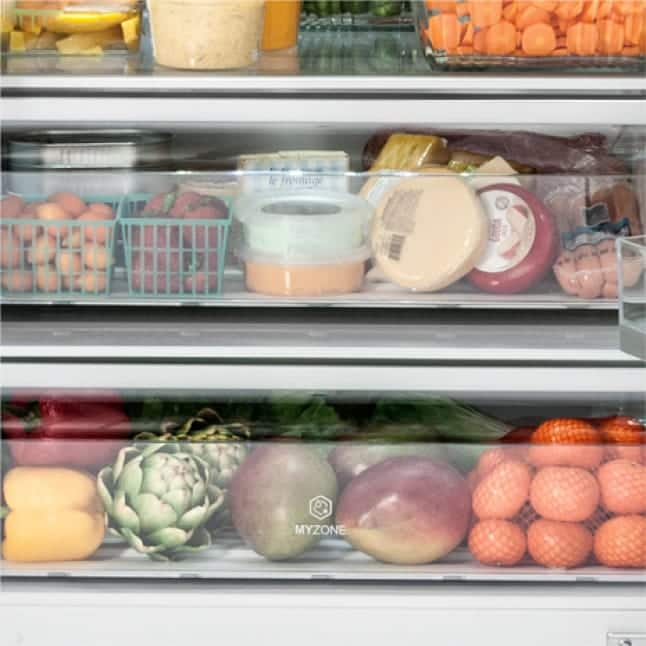 Tight shot of fruits and vegetables in crisper.