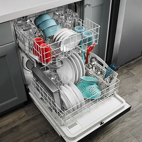 Open dishwasher showing a full load of dishes in both racks.