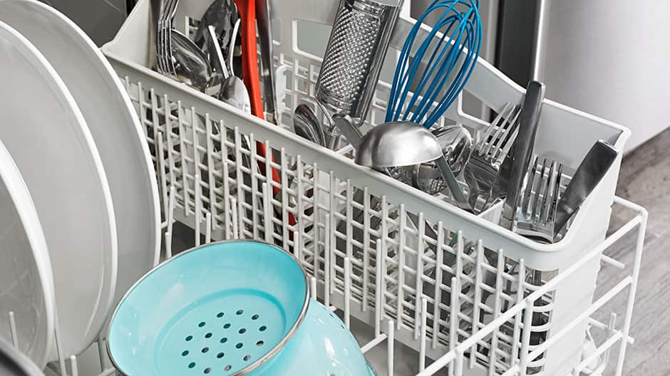 A white plastic utensil basket inside the dishwasher's lower rack contains assorted cutlery and utensils.