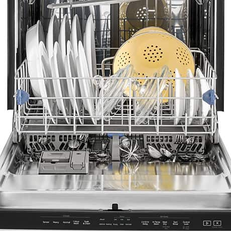 Fully loaded dishwasher with door open, lower rack out and Tap Touch controls easily visible along the top edge of the door.