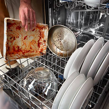 Man's hand placing dirty casserole dish in lower rack.