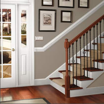 Bannister painted in brown, wrought-iron rail painted black