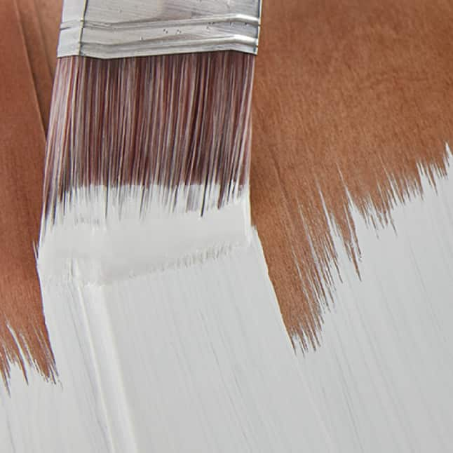 White paint being brushed onto wood substrate
