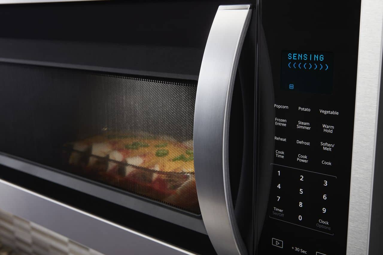Enchiladas cooking in the microwave with sensing displayed on the control panel.