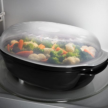 Covered dish of vegetables being steamed in the microwave.