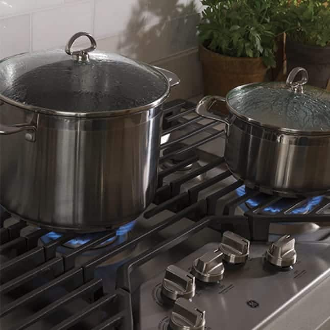 Two pots are cooking food over gas flames