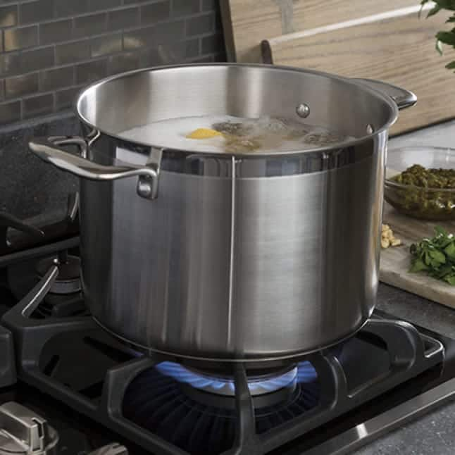A stock pot boils food over a gas flame