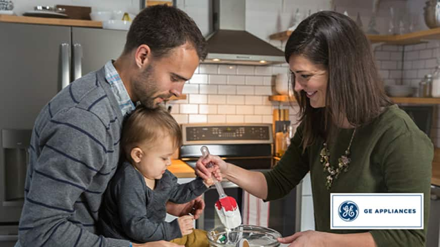 A family is in their kitchen together. The father holds the child up as the smiling mother guides the child's hand to stir a glass bowl of batter.