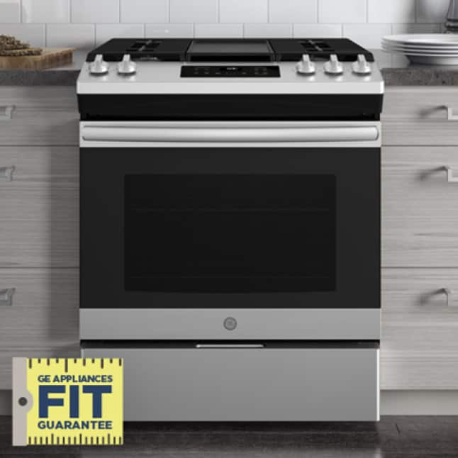 """A General Electric stainless steel stove fits perfectly between two gray counters. A logo in the corner reads GE Appliances Fit Guarantee."""""""