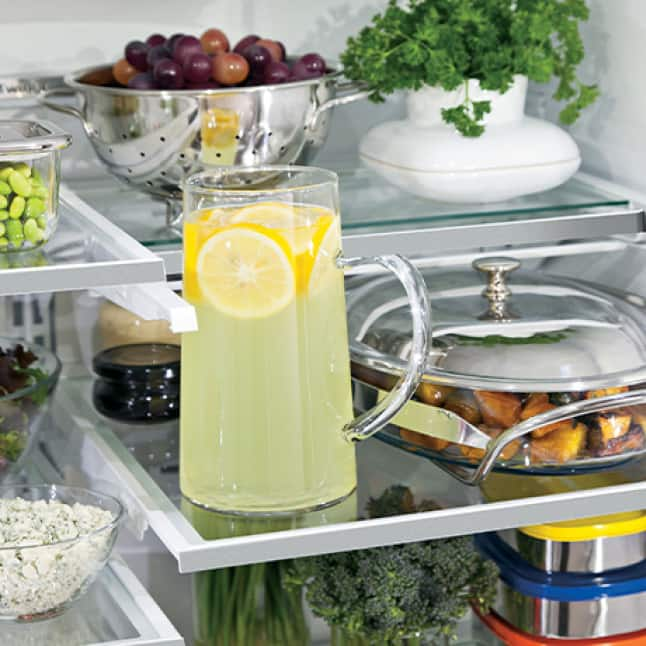 An interior shot of the fridge shows that the top shelf slid into itself, providing extra space to store a tall pitcher on the lower shelf