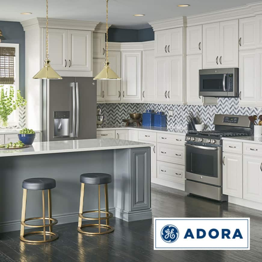 A cozy and stylish kitchen with several Adora appliances installed. The Adora logo is superimposed in the bottom-right corner.