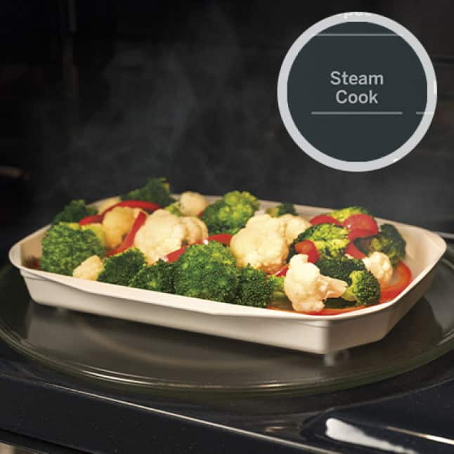 A tray of vegetables steam inside the microwave. A circular overlay shows the steam cook button on the panel.