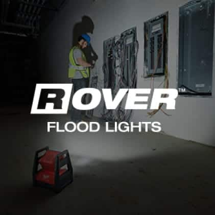 A man works on electrical box with ROVER Flood Light illuminating workspace from the floor.