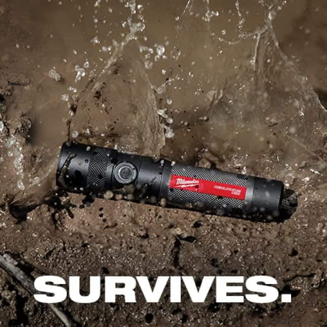 A Milwaukee flashlight lays on dirt surface.