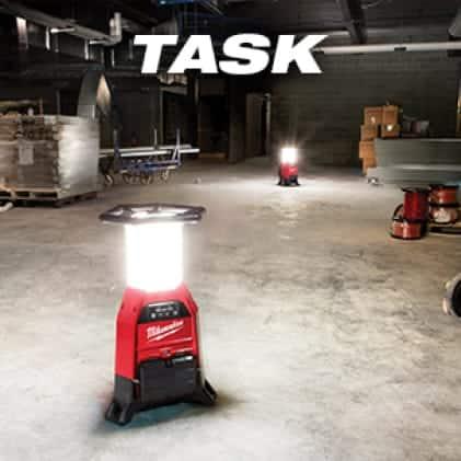 Two M18 RADIUS Site Lights on the floor provide light on a jobsite.