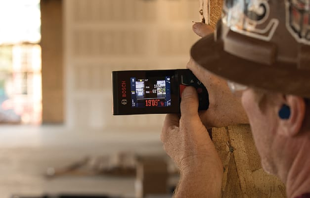 Bosch GLM400C being used to take measurement against wall.
