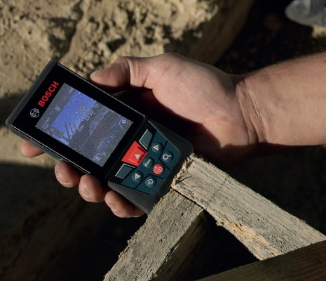 Bosch GLM400C being used to take outdoor measurement from a frame.