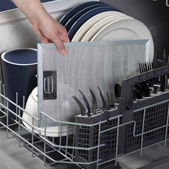 A hand places the dish safe filter into a dishwasher