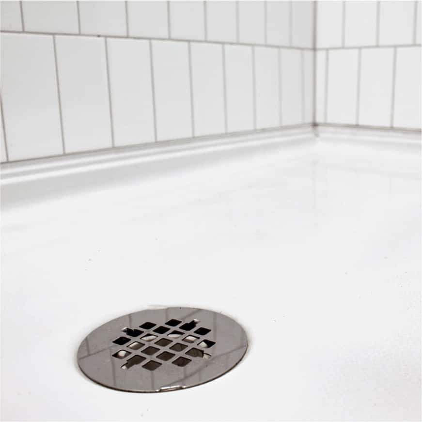 Preformed shower base with drain