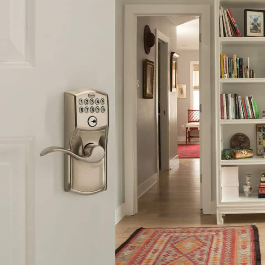 Schlage Camelot satin nickel keypad lever with Accent lever on white office door.
