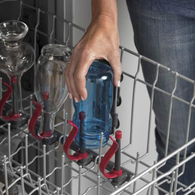 Someone loads glass and plastic bottles into their dishwasher. The bottle jets gently clamp the exterior and the nozzles go in the bottle's interior.