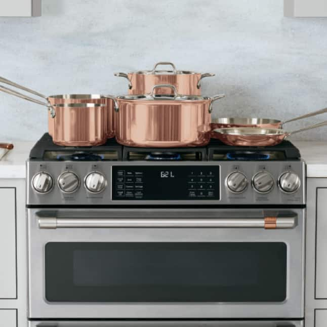 Head on image of gas range with copper pots and pans on the cooktop