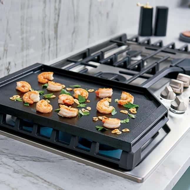 Shrimp cooks over a flame on the griddle