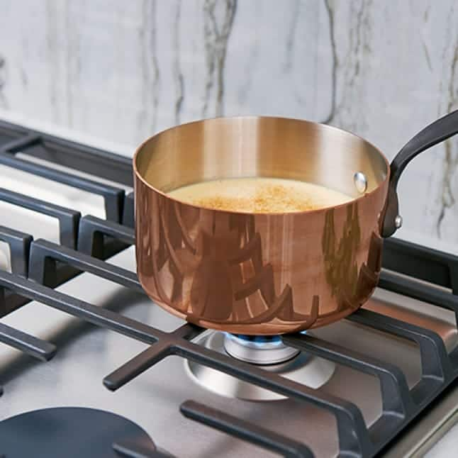 A copper pot simmers over a small flame on the cooktop