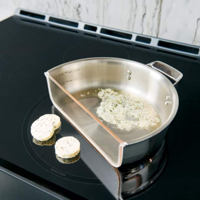 Discs of cheese sit next to a pan that's been cut in half. The cheese sitting on the induction element is solid, while cheese in the pan has melted.
