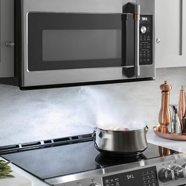 Steam rises from a stainless steel pot boiling vegetables on a Café range. The microwave above draws in the steam.