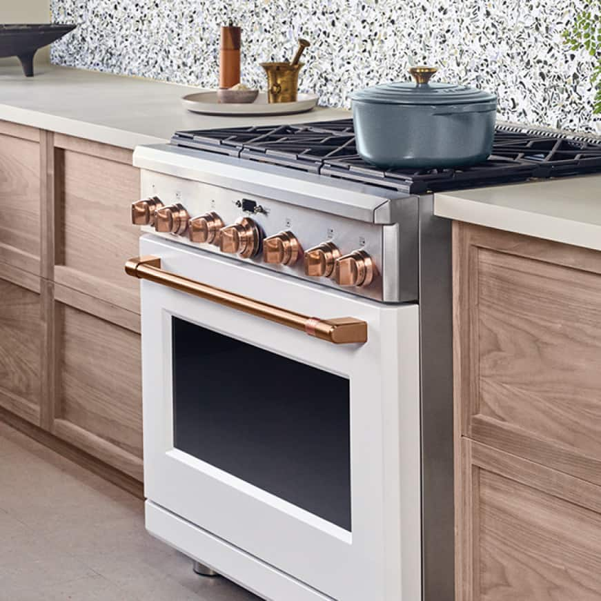 An enamel pot sits on a matte white Café range with brushed copper trim. The stylish copper complements the wood cabinets and modern stone backsplash.