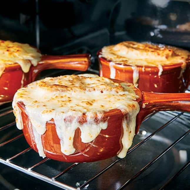 Golden-brown cheese melts over the rim of three ramekins cooking on a wire rack in the convection microwave oven.