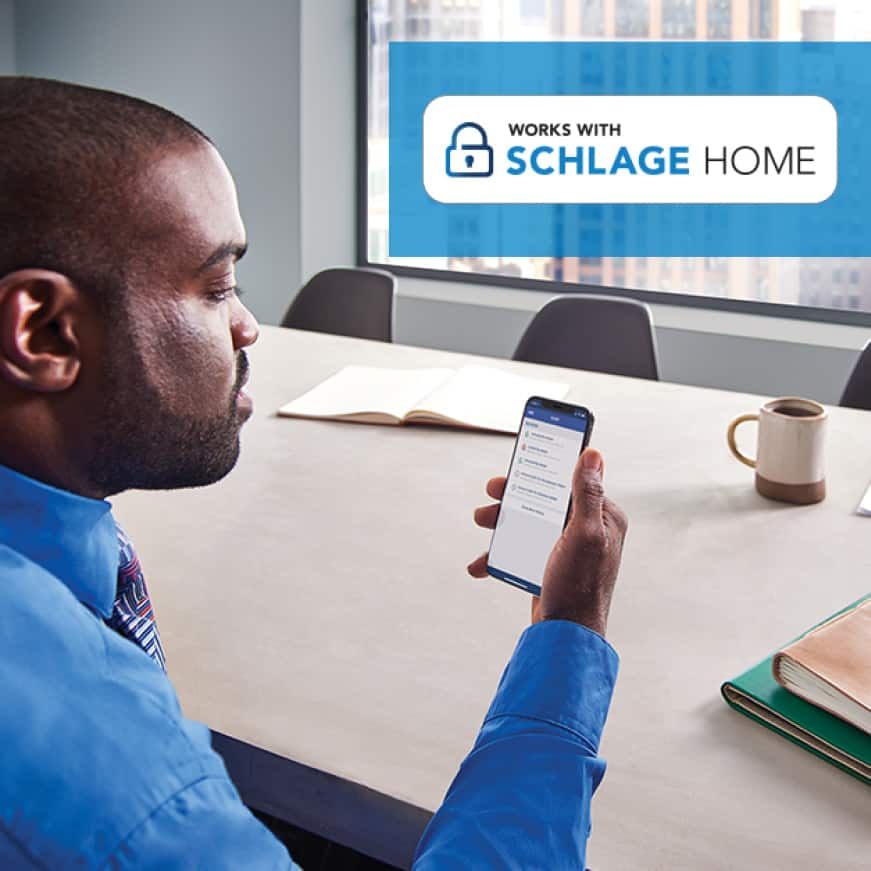Man checking smartphone with Schlage Home app from work.