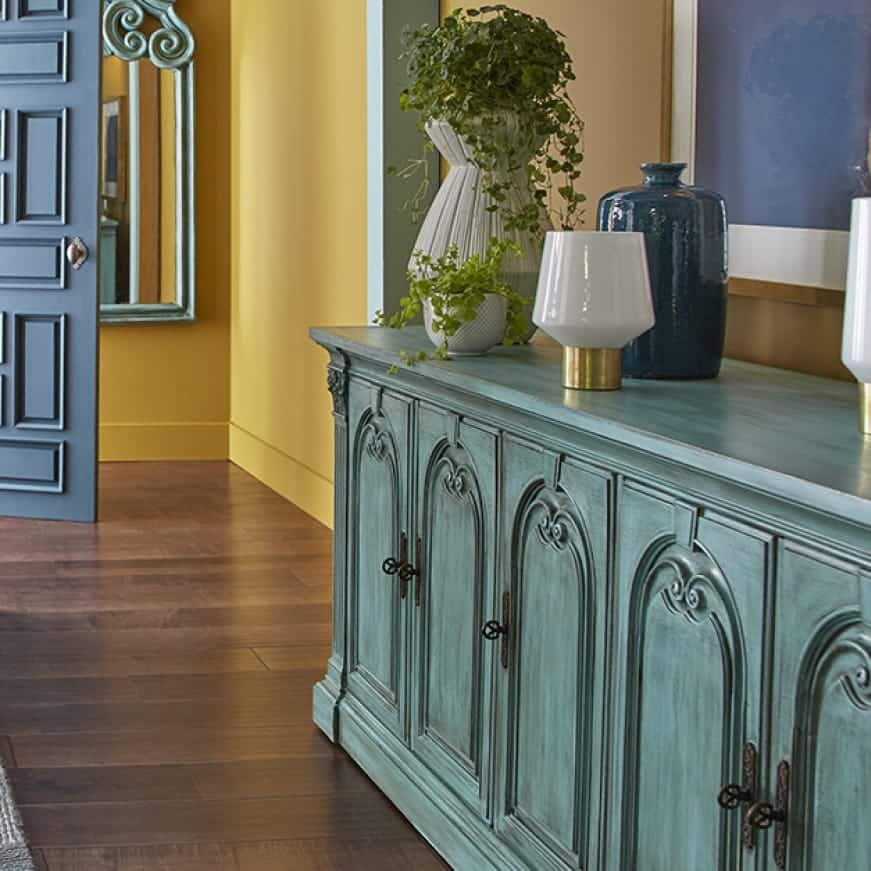 Dresser painted with a chalk green finish, shown in a front doorway entrance