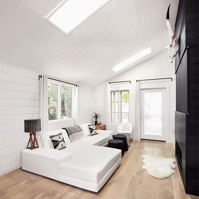 A sitting room with vaulted ceiling and skylights with the white timeless shiplap boards on the ceiling and walls