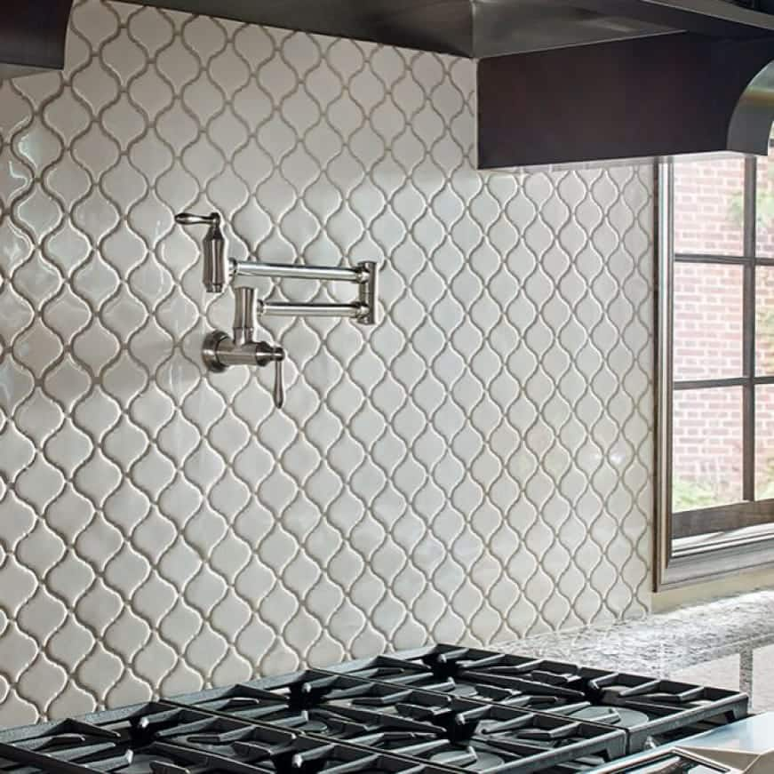 A lifestyle image showing the enhanced look of the kitchen with white arabesque mosaic on a kitchen backsplash.