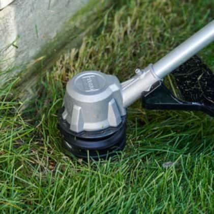 Trimmer head cutting grass close-up