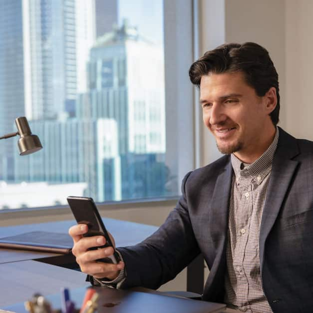 Man sitting in office looking at smartphone.