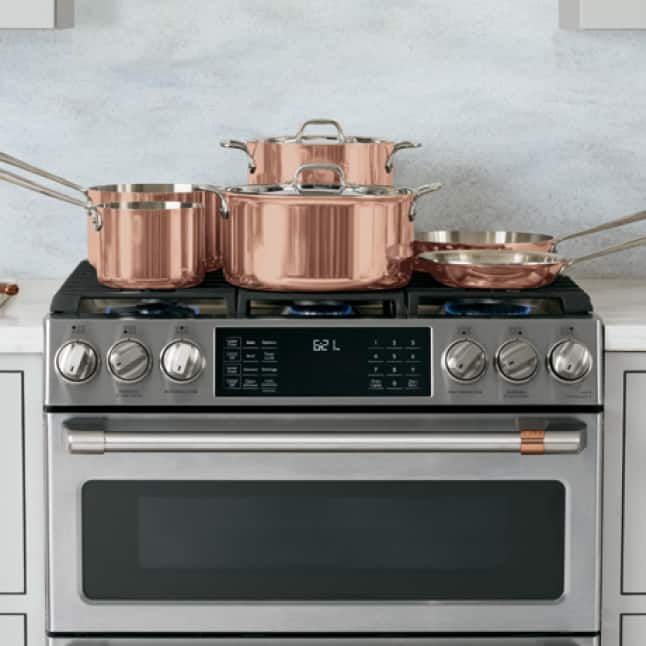 A variety of cookware fills up a stainless Cafe range from edge-to-edge, fitting a total of six medium to large-size pots and pans.