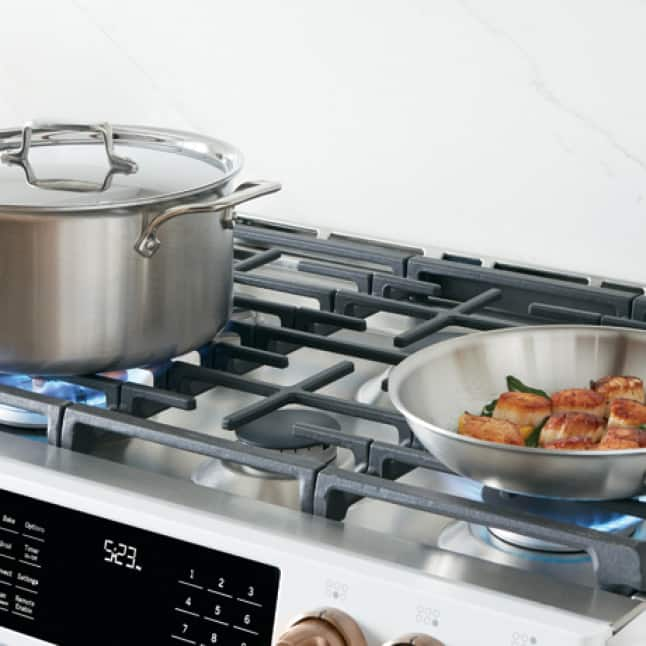 A stainless steel pot and pan cook on top of two activated burners.