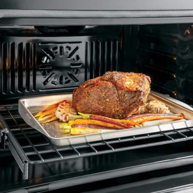 A roast is pulled out of the oven.The convection fan is clearly visible in the back of the cavity.