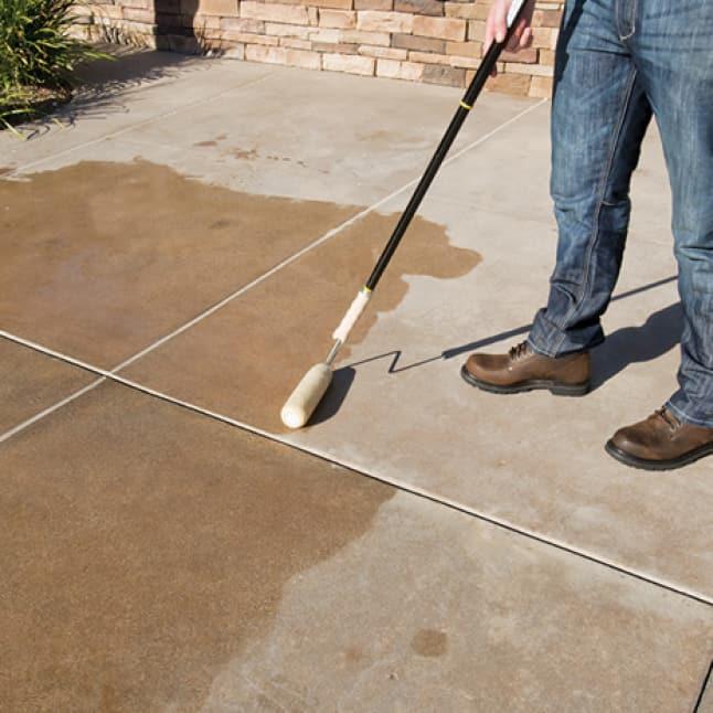 Concrete floor being primed with BEHR PREMIUM Concrete Bonding Primer