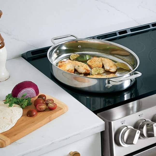 Food cooks on a large pan that covers the two SyncBurners.