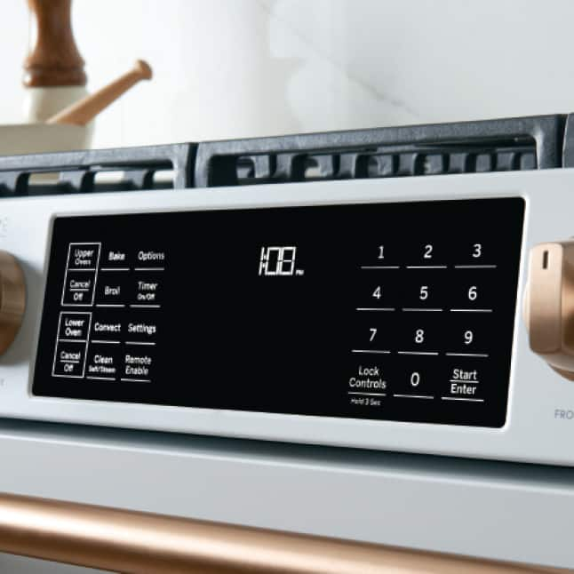 Angled image of Matte White gas range with a tight crop on backlit control panel