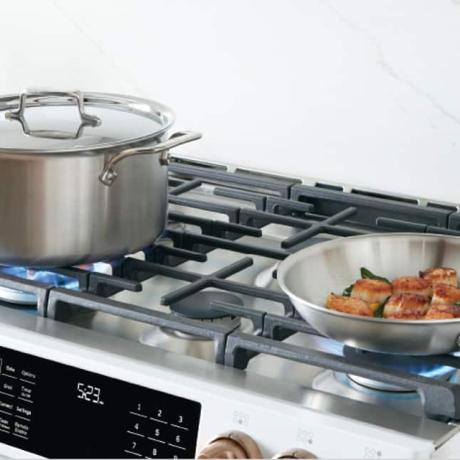 Angled image of Matte White gas range showing front two burners with food